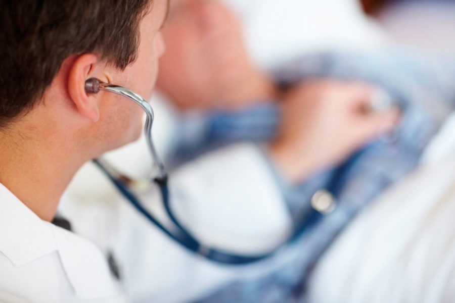 Доктор прослушивает пациента