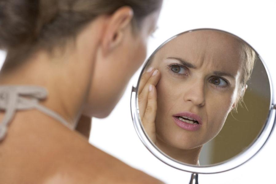 Женщина смотрит на свое лицо в зеркале