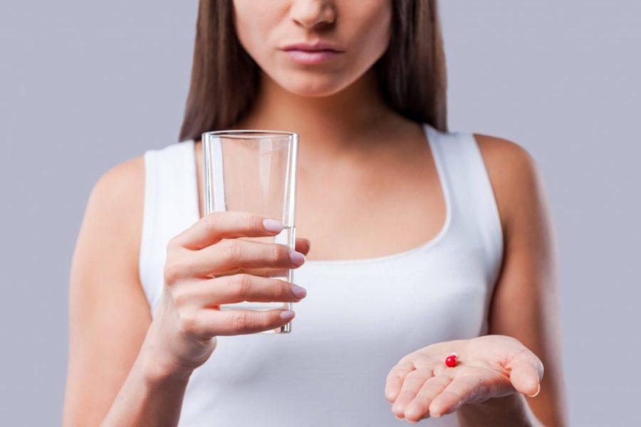 Девушка держит таблетку и стакан воды в руках