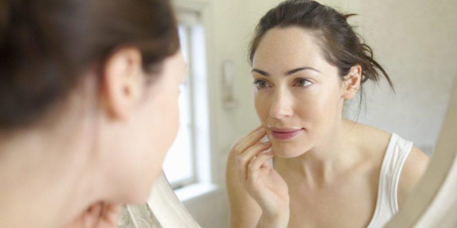 Девушка смотрит в зеркало на свое лицо